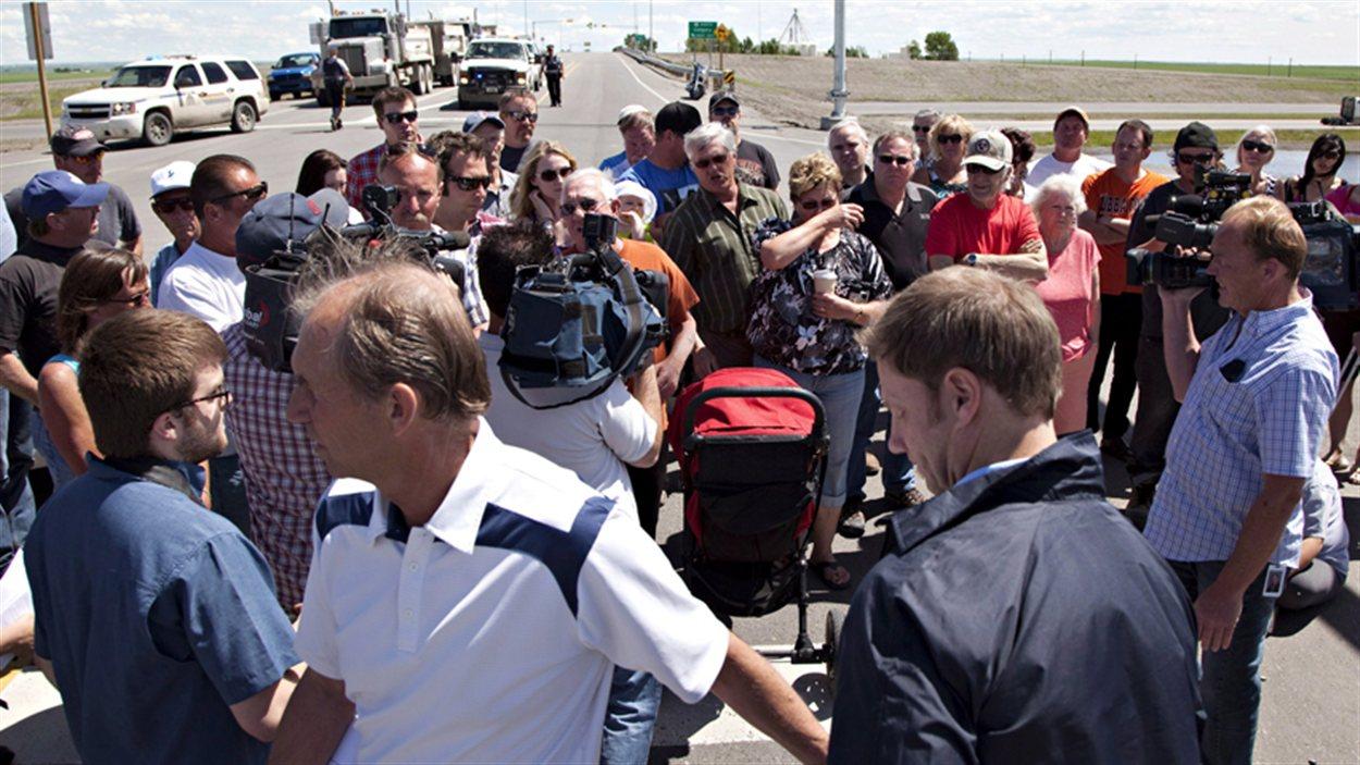Le maire de High River (en bas, à gauche) fuit une foule de résidents frustrés d'être tenus loin de leur logement.