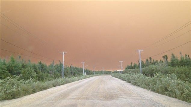 Le ciel est orange au-dessus du village d'Eastmain, qui a dû être évacué en raison de la fumée causée par un feu de forêt.