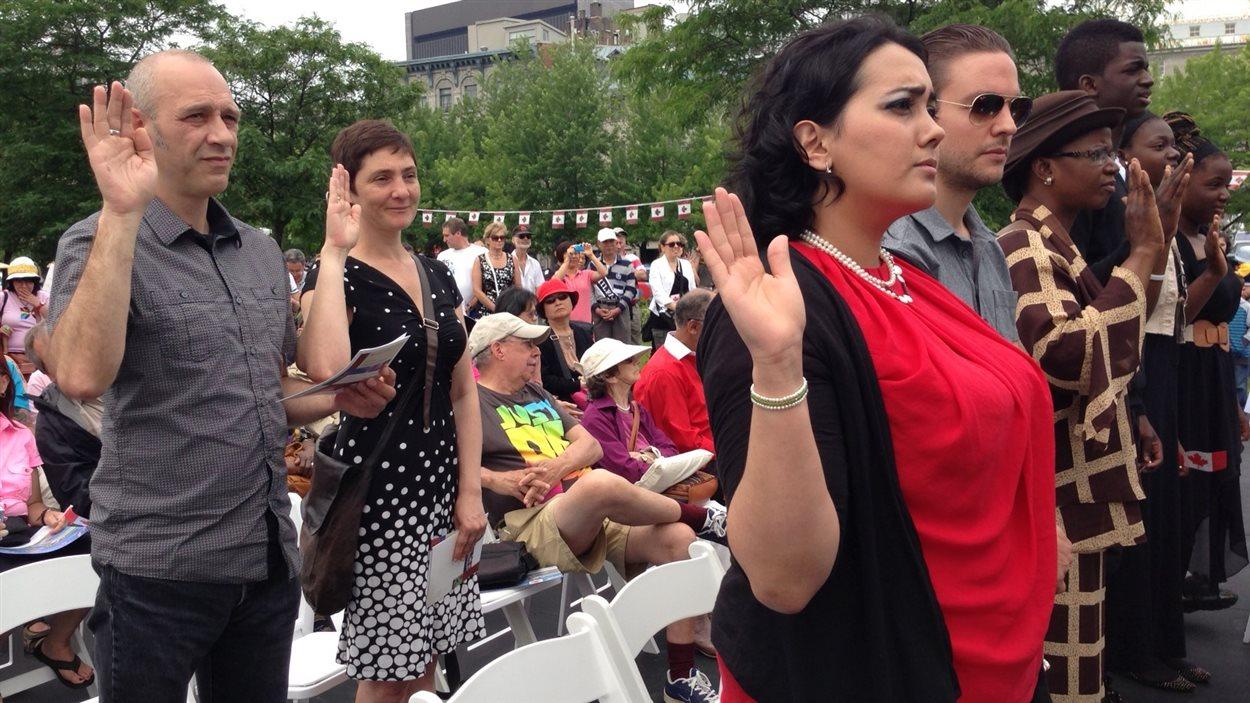 De nouveaux citoyens canadiens prêtent serment à la reine.