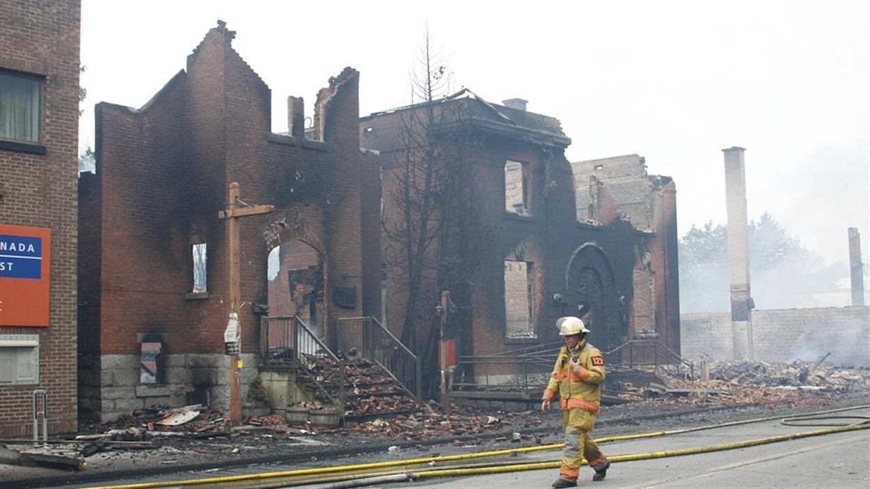 Un pompier marche dans une rue dévastée par les flammes.