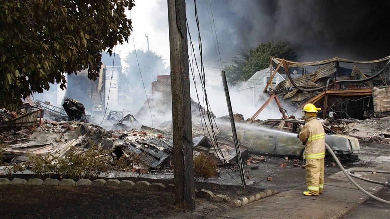 Un pompier arrose les décombres de l'une des nombreuses maisons rasées pa rles flammes.