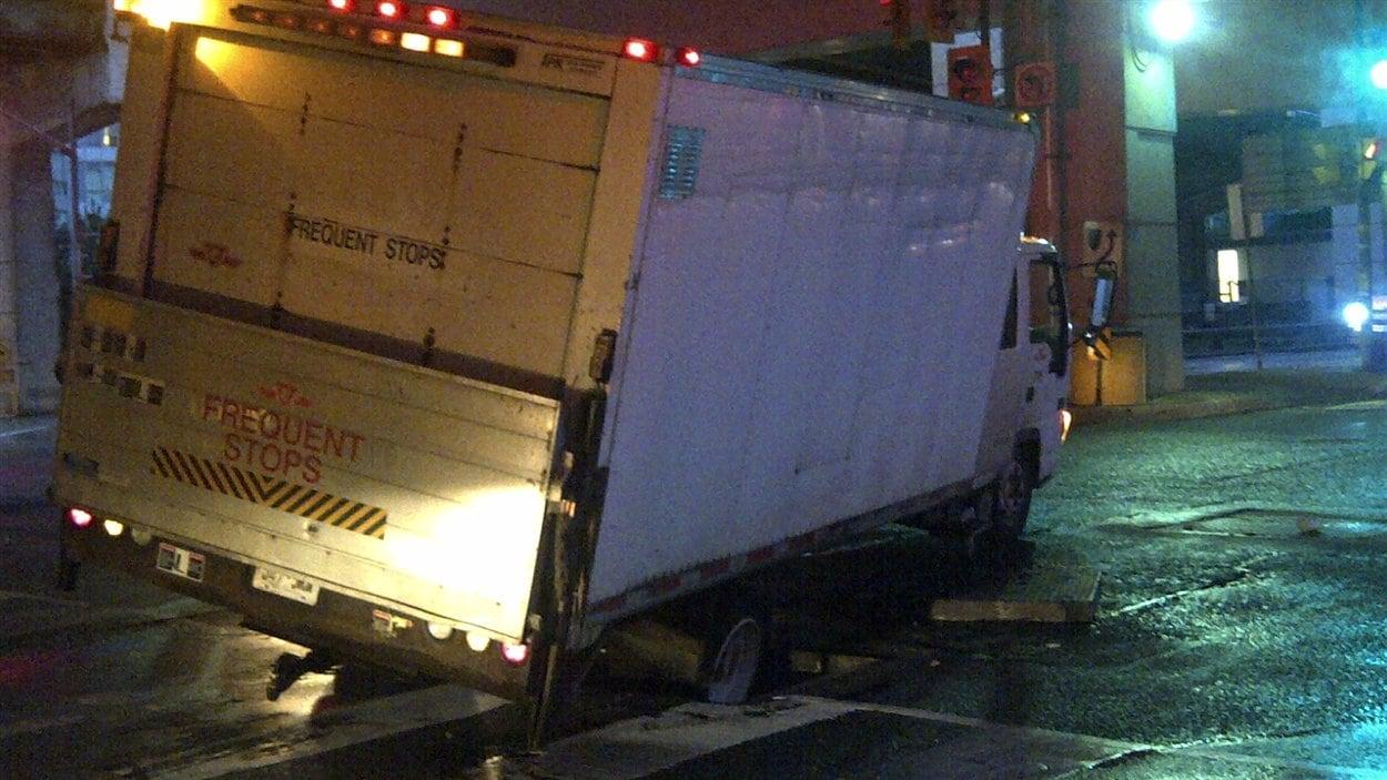 Un camion est tombé dans une bouche d'égout dont le couvercle avait été soulevé par l'eau.