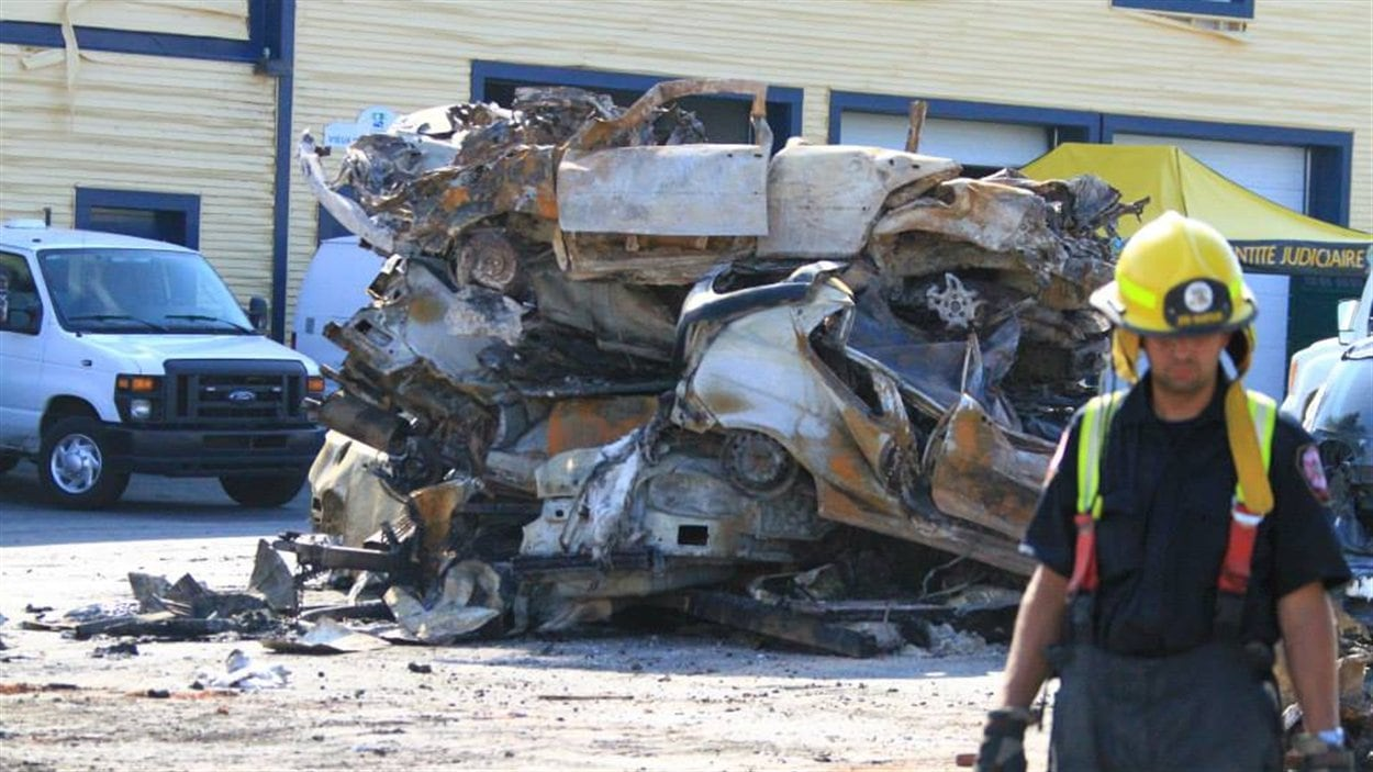 Des voitures complètement calcinées sont empilées alors que les pompiers s'activent encore parmi les décombres.