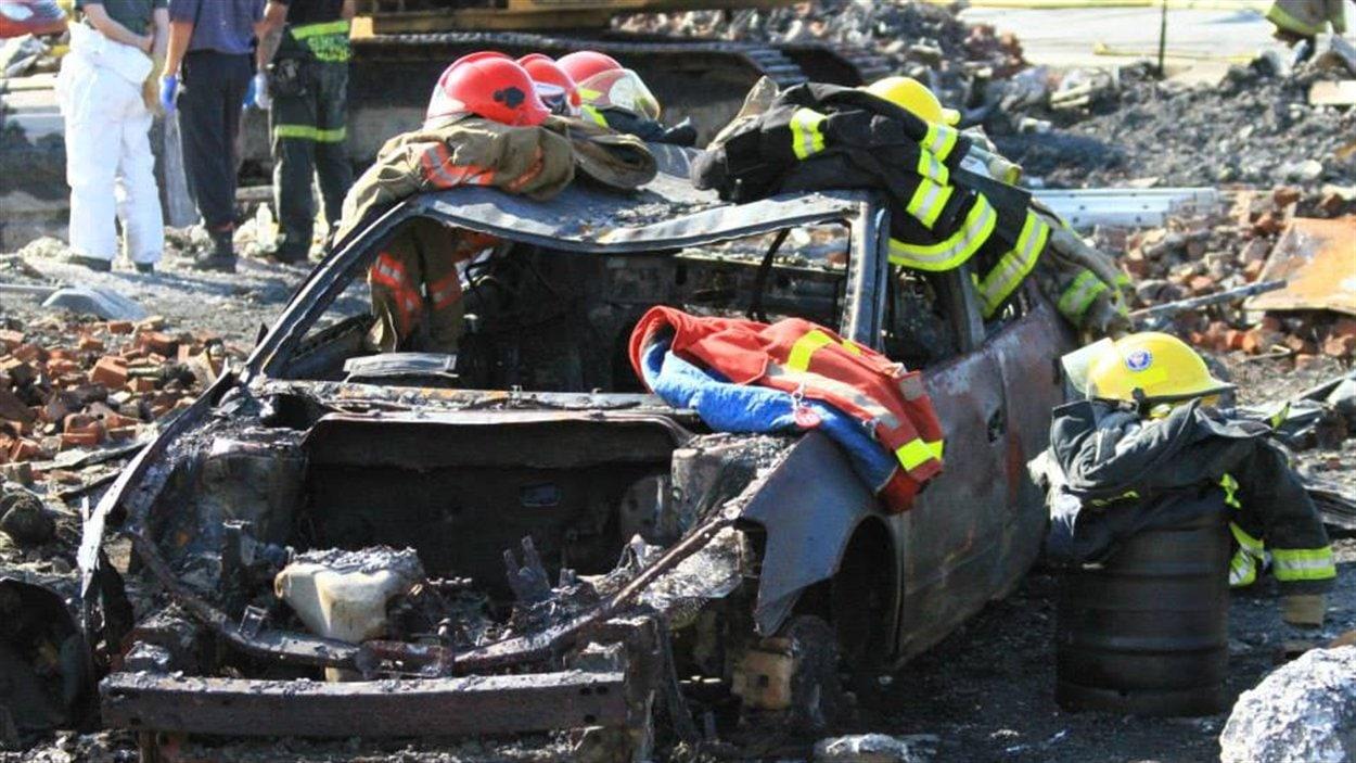 Des pompiers ont déposé leurs habits sur une voiture complètement carbonisée.
