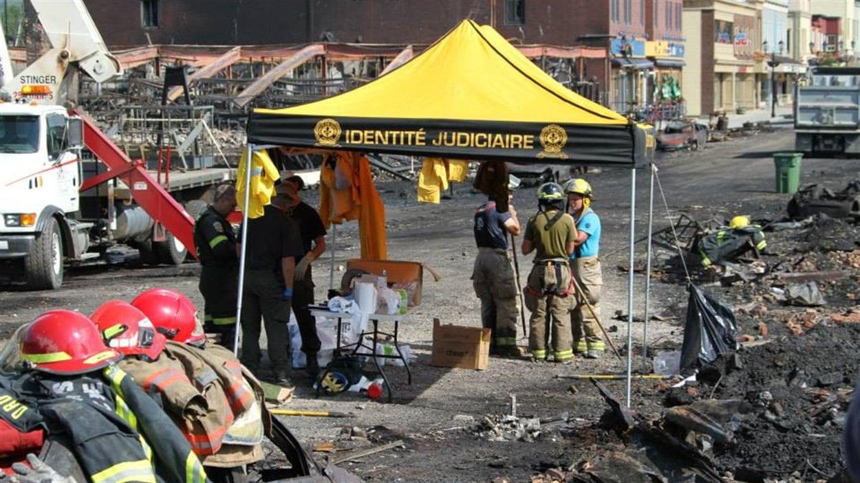 Une tente « Identité judiciaire » jaune et noire trône au milieu des débris calcinés.