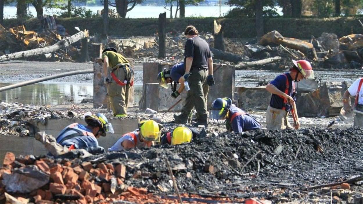 Des pompiers fouillent dans les restes de la locomotive qui a explosé au centre-ville de Lac-Mégantic.
