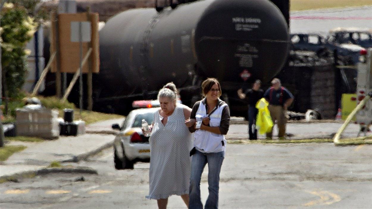 Une volontaire escorte l'une des nombreuses personnes évacuées afin qu'elle puisse récupérer des objets laissés chez elle (8 juillet 2013).