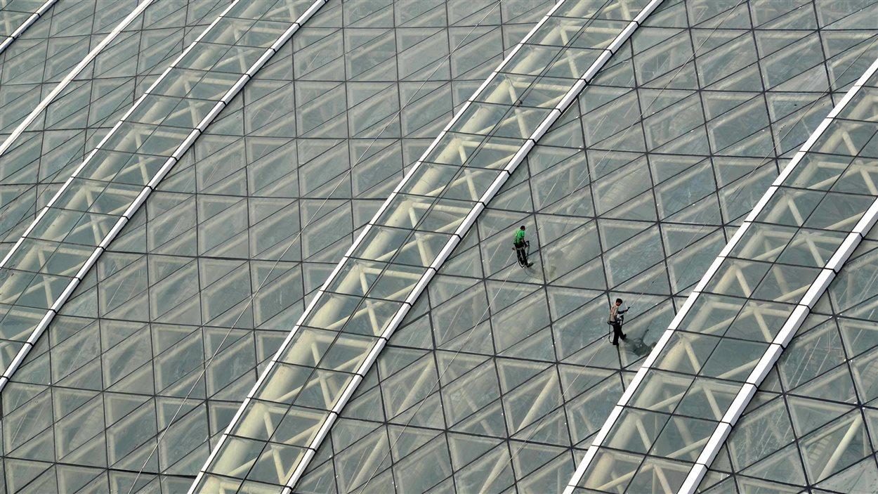 Des travailleurs nettoient le plafond vitré du New Century Global Center, à Chengdu, le 28 juin 2013
