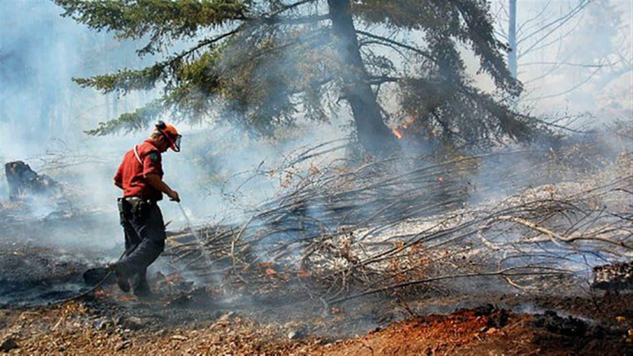 Un pompier éteint un feu de forêt en Colombie-Britannique