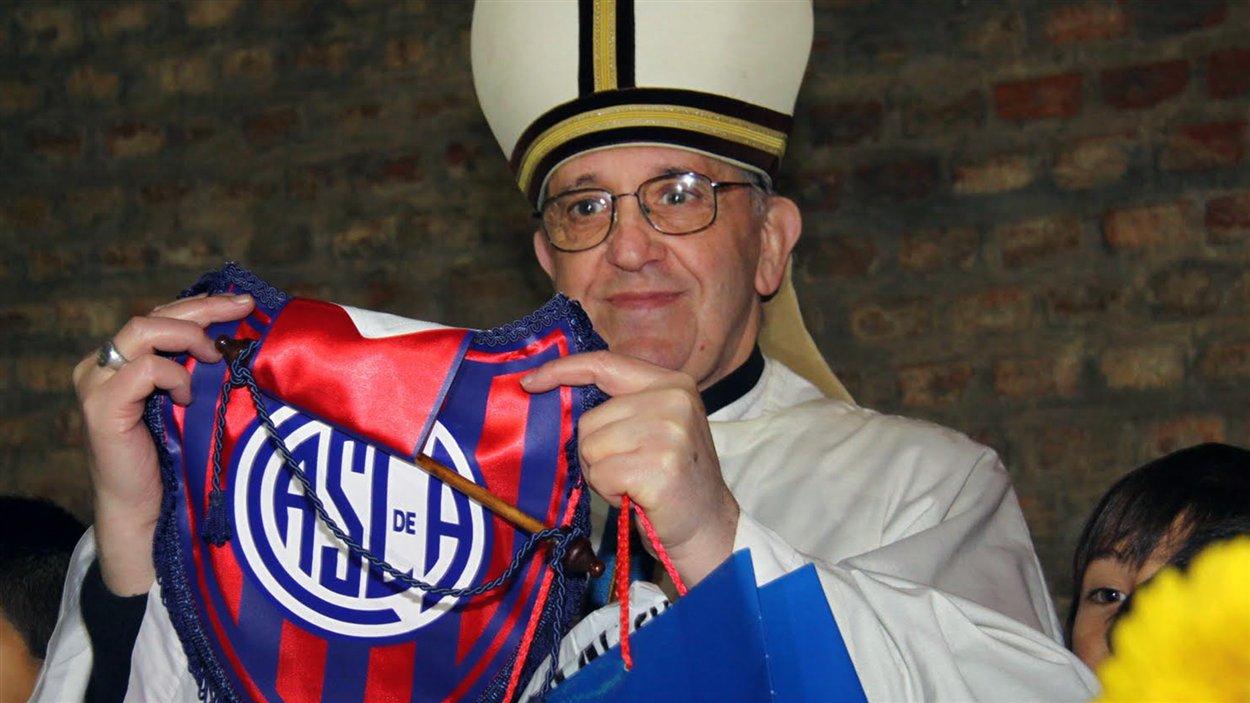 Le cardinal argentin Jorge Mario Bergoglio tient un emblème du club de soccer San Lorenzo, dont il est un fan.