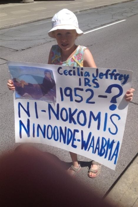 Une jeune participante à l'événement Honour the Apology à Gatineau tient une affiche, le 25 juillet 2013.