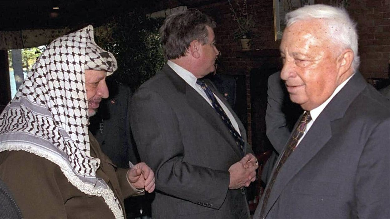 (21 octobre 1998) Ariel Sharon en compagnie du leader palestinien Yasser Arafat durant la reprise des négociations du processus de paix, à Wye Plantation, dans l'État du Maryland.