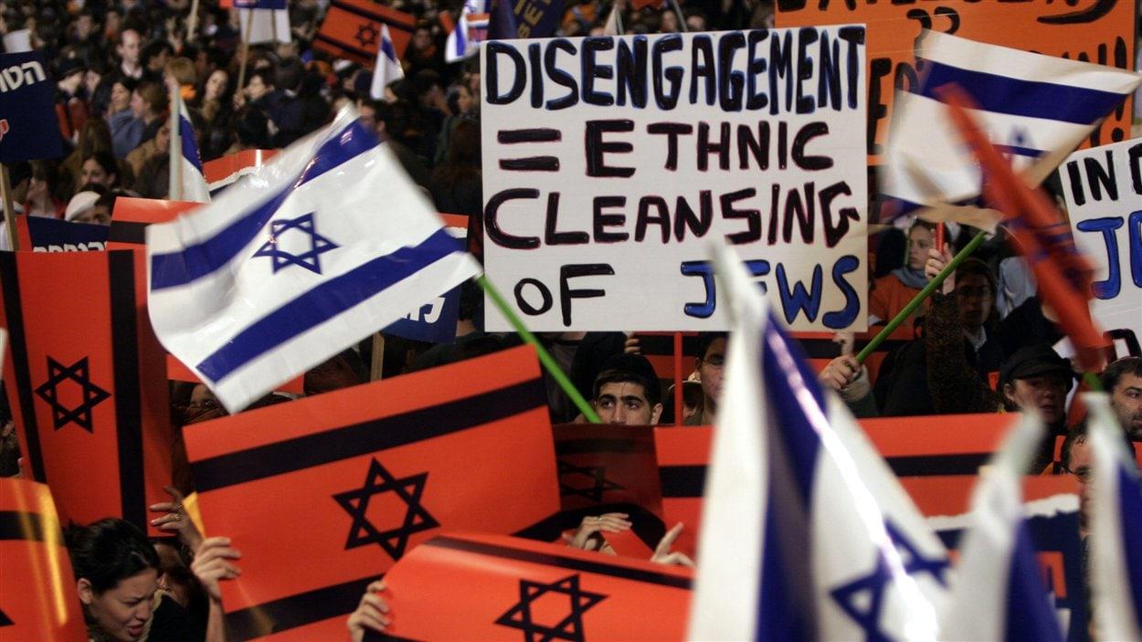 (30 janvier 2005) Quelque 130 000 manifestants se sont réunis afin de dénoncer le plan de retrait de la bande de Gaza d'Ariel Sharon. La plupart sont des colons israéliens. Sur l'affiche, on peut lire : «Retrait = nettoyage ethnique des Juifs».