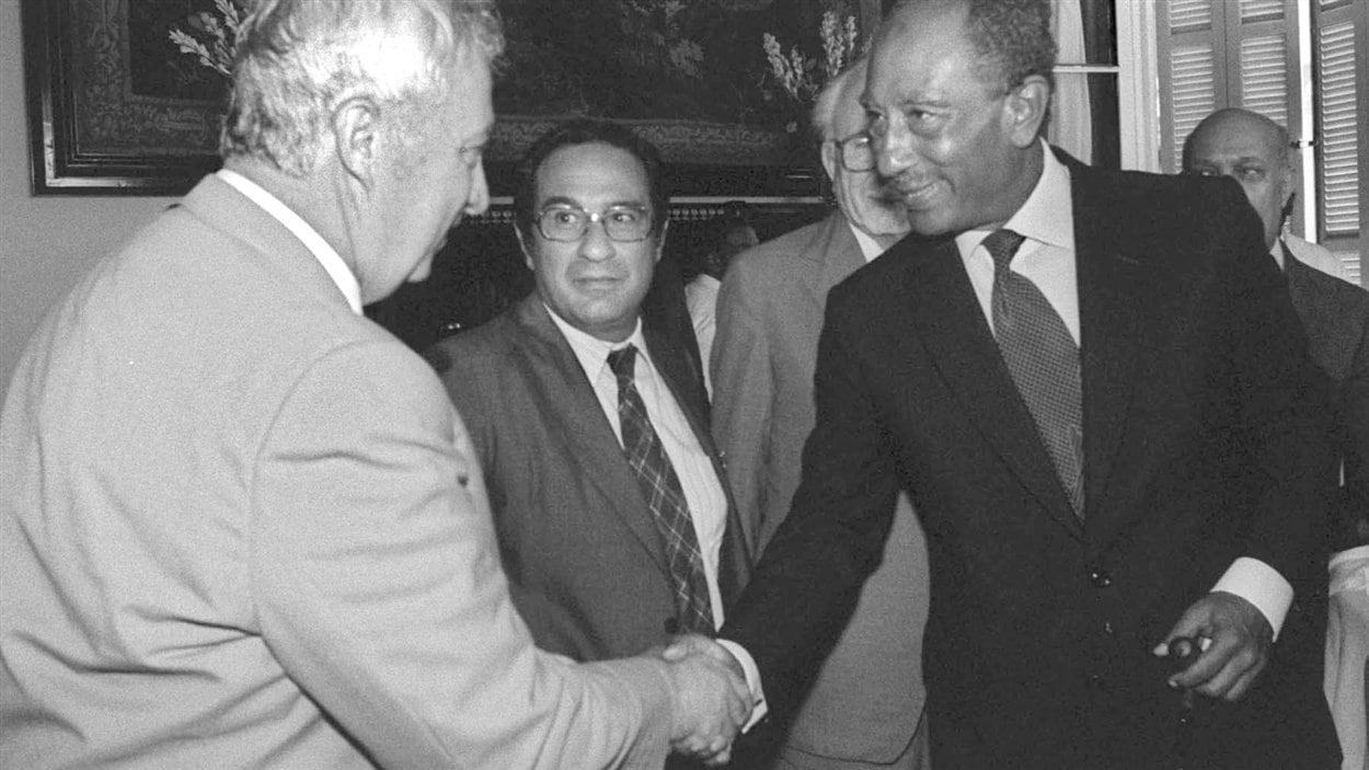 (25 août 1981) Le ministre israélien de la Défense Ariel Sharon serre la main au président égyptien Anouar El-Sadate, à Alexandrie.