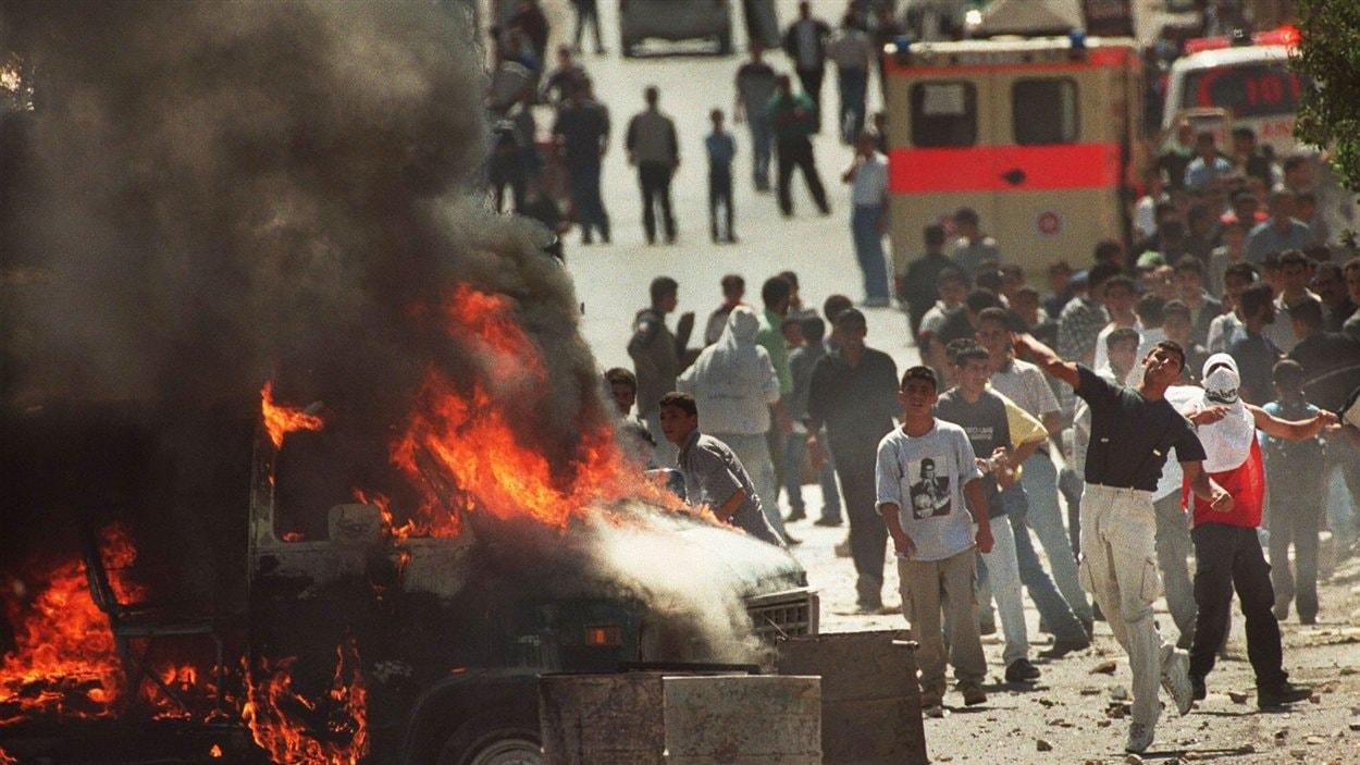 (30 septembre 2000) De jeunes Palestiniens jettent des pierres sur les troupes israéliennes dans la ville de Bethléem, en Cisjordanie. C'est la deuxième Intifada, ou « guerre des pierres ».