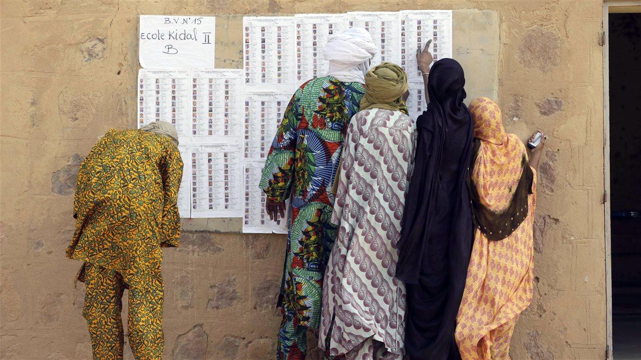 À Kidal, dans le nord du Mali, des électeurs cherchent leurs noms à l'entrée du bureau de vote, le 28 juillet 2013
