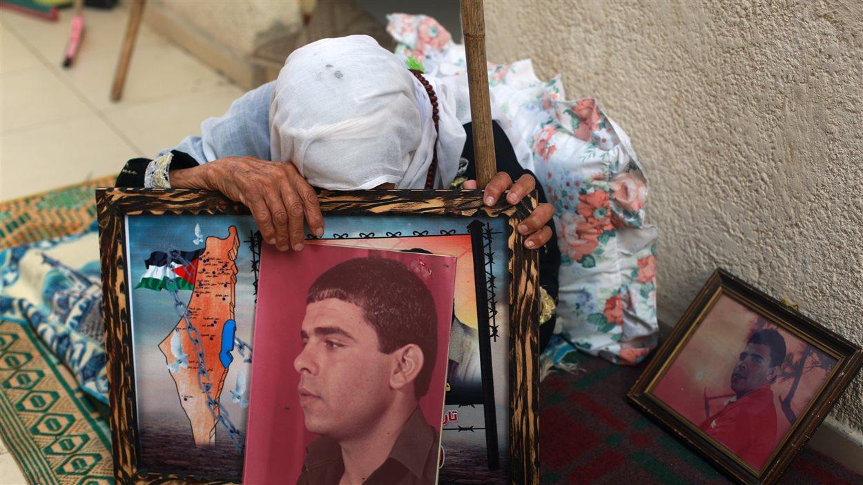 La mère du Palestinien Fares Bound, détenu dans une prison israélienne depuis 22 ans, pleure en tenant la photo de son fils après avoir appris la nouvelle de sa possible libération, le 28 juillet 2013