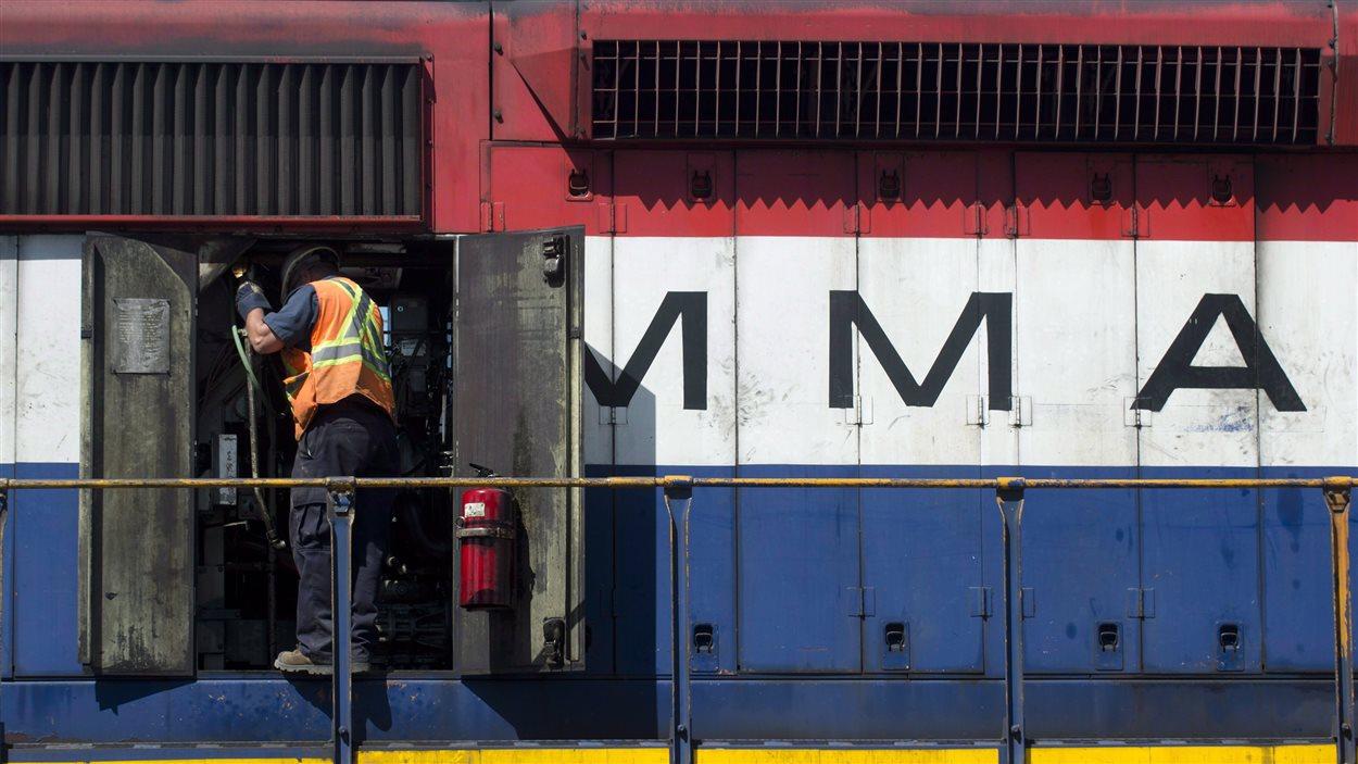 Un mécanicien vérifie le moteur d'une locomotive de la Montreal, Maine & Atlantic Railway (MMA) à l'extérieur des bureaux de la compagnie, à Farnham, le 11 juillet 2013