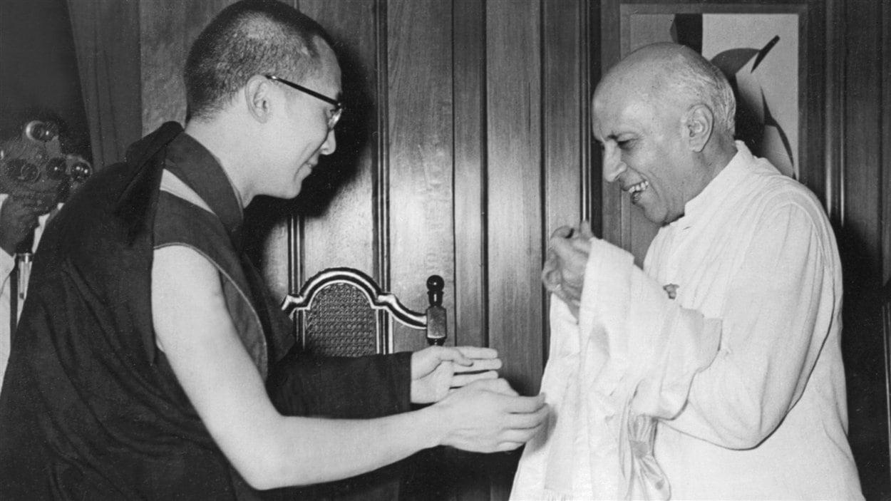 (7 septembre 1959) Le dalaï-lama offre une écharpe traditionnelle tibétaine au premier ministre indien de l'époque, Jawaharlal Nehru.