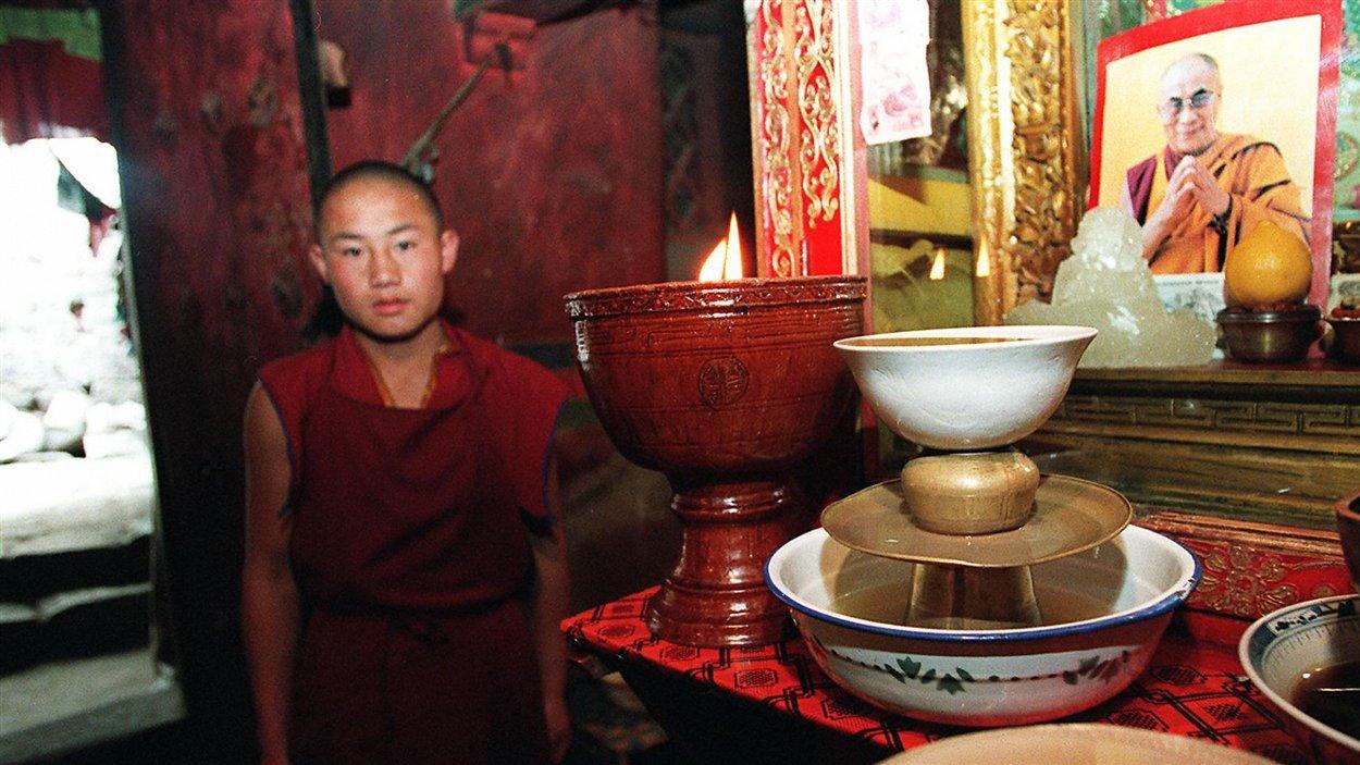 (23 février 1997) À Lhassa, la capitale tibétaine, un moine garde un oeil sur l'un des portraits du dalaï-lama. Il s'agit de l'un des rares monastères à garder une photo de leur guide spirituel, car la pratique est interdite par Pékin depuis 1996.