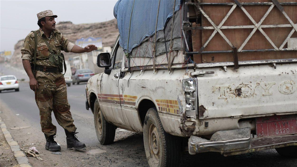 Un soldat yéménite procède à un contrôle de sécurité près de l'ambassade américaine à Sanaa