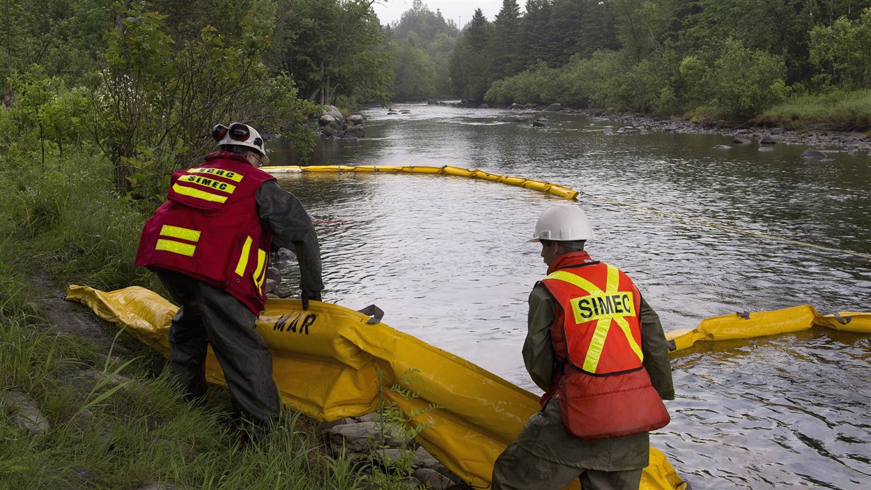 Des travailleurs procèdent au nettoyage de la rivière Chaudière après le déversement causé par la tragédie ferroviaire de Lac-Mégantic, le 9 juillet dernier