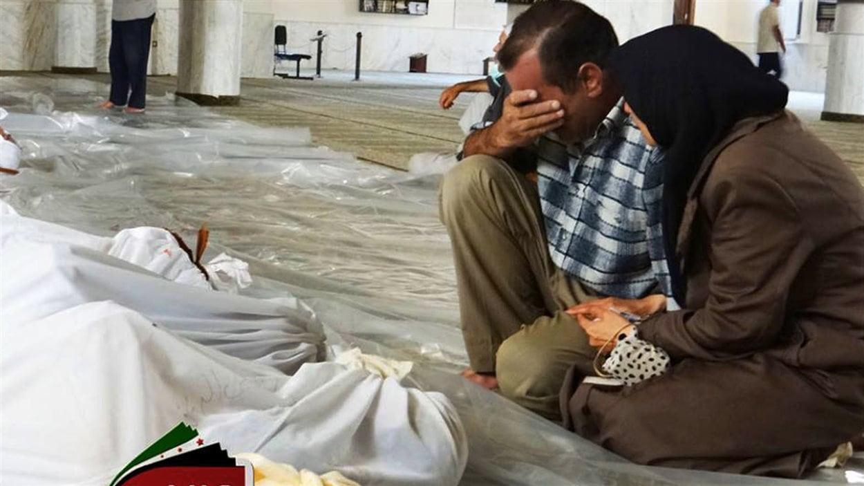 Une image diffusée par un groupe d'opposants syriens montre un homme et une femme près de corps de présumées victimes d'une attaque chimique, près de Damas, le 21 août.