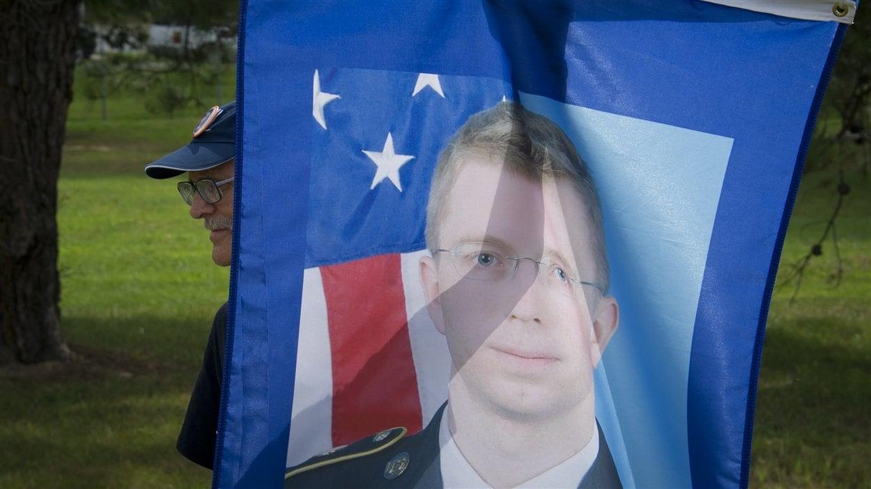 Un partisan de Bradley Manning brandit une affiche du soldat américain devant la cour martiale le 21 août 2013, où il attend sa peine.