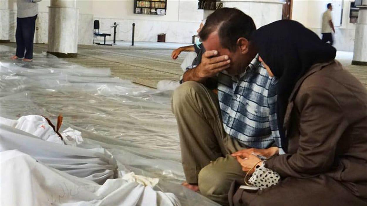 Un homme et une femme pleurent un enfant mort le mercredi 21 août dans ce que l'opposition syrienne qualifie « d'attaque au gaz neurotoxique ».