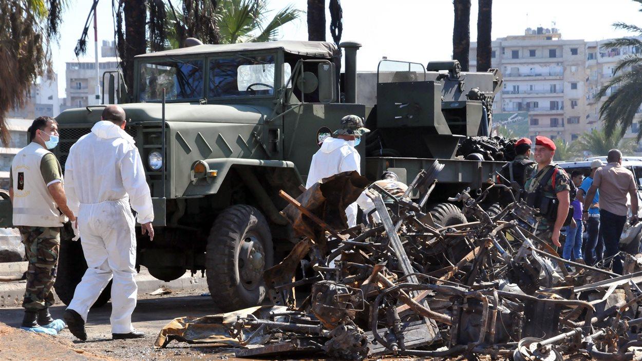 Des carcasses des voitures sont fouillées par les autorités libanaises, après l'attaque de Tripoli.