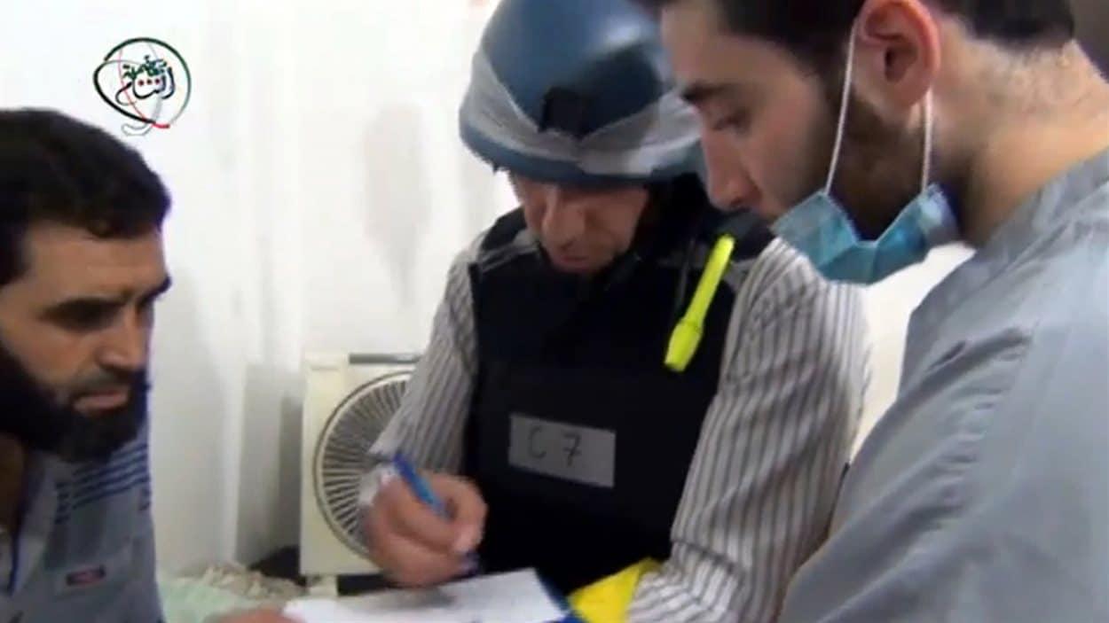 Cette photo fournie par les opposants au régime syrien montrerait des inspecteurs de l'ONU en discussion avec un blessé de la présumée attaque chimique. Son authenticité ne peut être vérifiée par des sources.