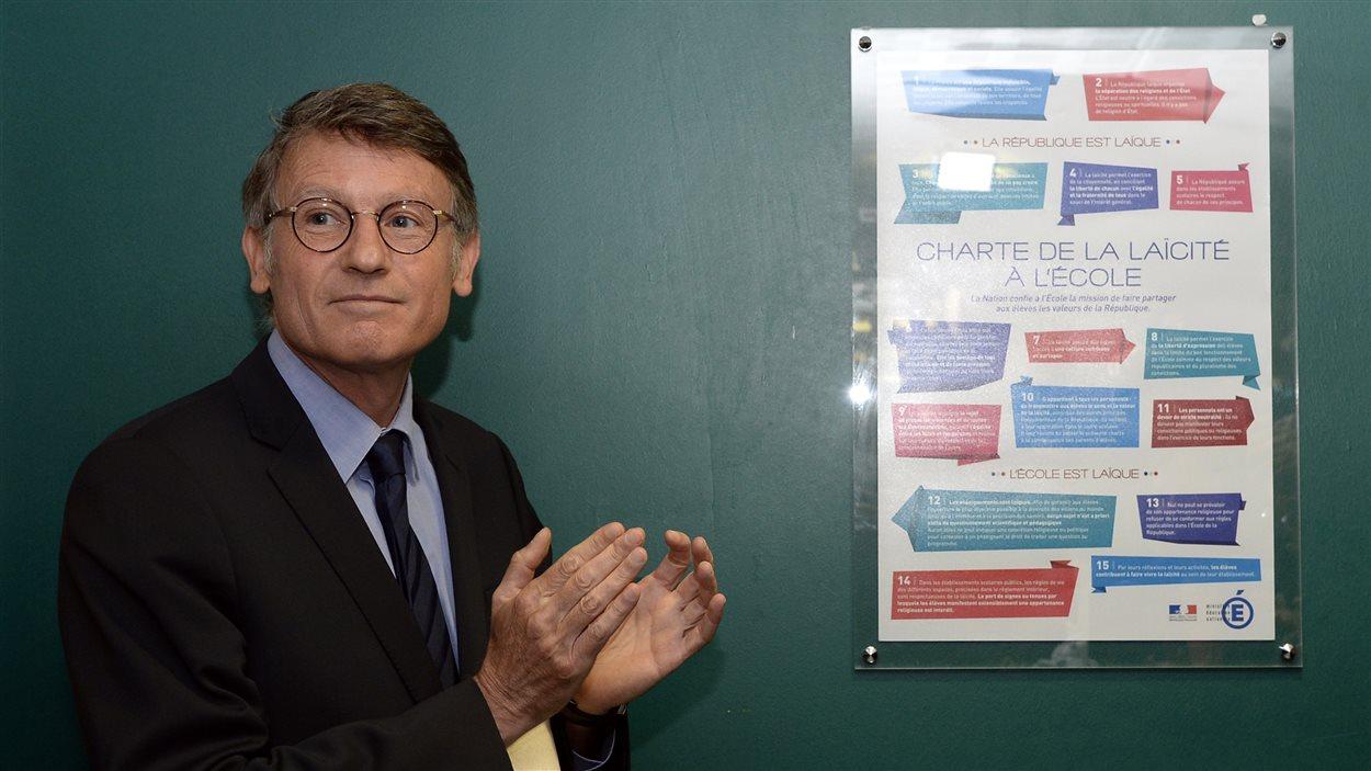 Le ministre de l'Éducation français, Vincent Peillon, devant l'affiche rappelant aux élèves les règles de laïcité en vigueur dans leur école.