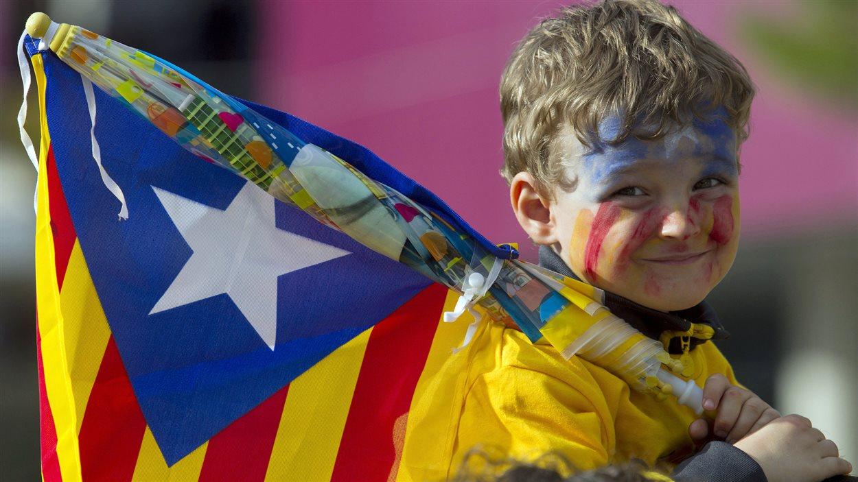 Un jeune garçon tient le drapeau catalan lors d'une grande manifestation du mouvement indépendantiste, le 11 septembre 2013.