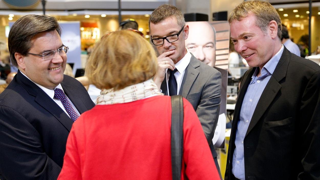 Les candidats Denis Coderre (à gauche) et Philippe Schnobb (à l'extrême-droite) discutent avec une citoyenne.