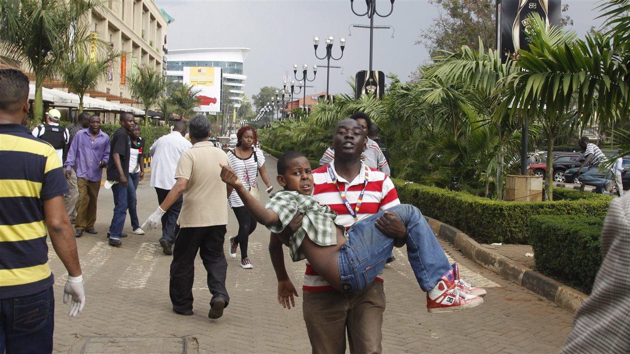 Un secouriste aide un enfant devant le centre commercial de Nairobi.