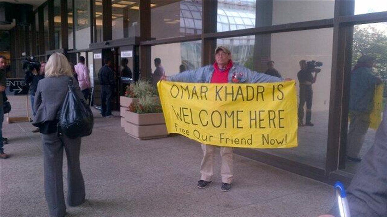 Un partisan d'Omar Khadr tient une banderole sur laquelle est écrit : « Omar Khadr est le bienvenu ici, libérez notre ami maintenant! », devant le palais de justice d'Edmonton, le 23 septembre 2013.