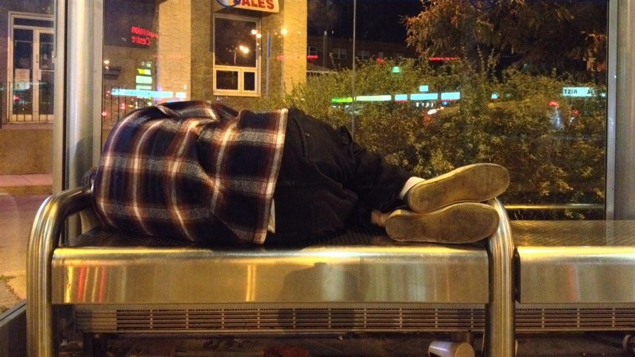 Une personne sans-abri dort à un arrêt d'autobus de la Régie des transports de Winnipeg, le matin du 23 septembre 2013.
