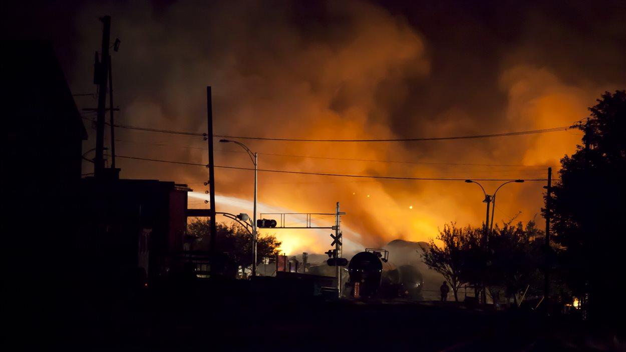 Les pompiers arrosent le brasier suite au déraillement tragique à Lac-Mégantic.