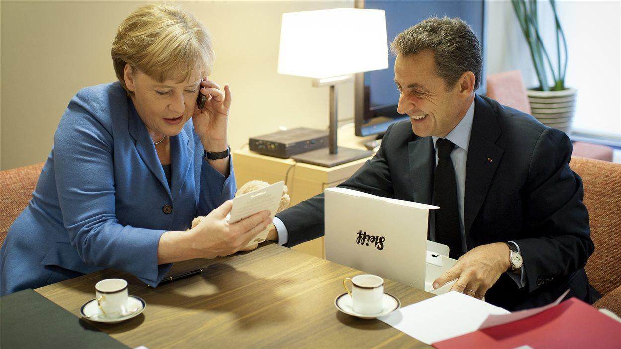 La chancelière allemande, Angela Merkel, parle au téléphone à Carla Bruni-Sarkozy peu après la naissance de sa fille, le 23 octobre 2011. Elle est accompagnée du président français, Nicolas Sarkozy.