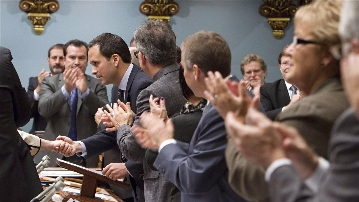 Les députés du Parti québécois applaudissent le ministre des Affaires intergouvernementales, Alexandre Cloutier, après la présentation de la motion blâmant le gouvernement fédéral pour son « intrusion » dans la démocratie québécoise, le 23 octobre 2013.