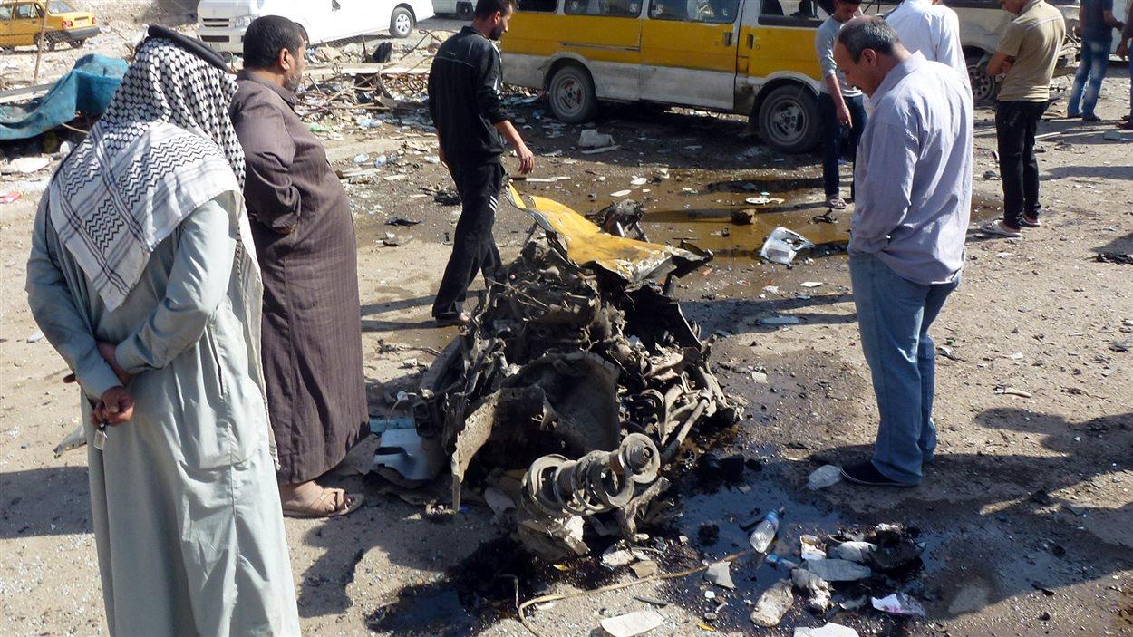 Des Irakiens inspectent la carcasse d'un véhicule à la suite d'un attentat commis dans le quartier Mashtal de Bagdad, le 27 octobre.