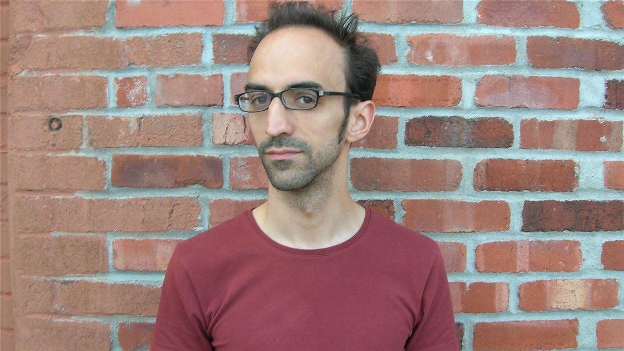 Portrait en couleur de l'auteur David Clerson. Le jeune homme est photographié devant un mur de briques, il porte des lunettes et un t-shirt couleur brique.