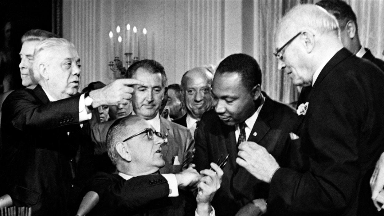 Lyndon B. Johnson tend la main à Martin Luther King après la signature du projet de loi historique sur les droits civils, le 2 juillet 1964.