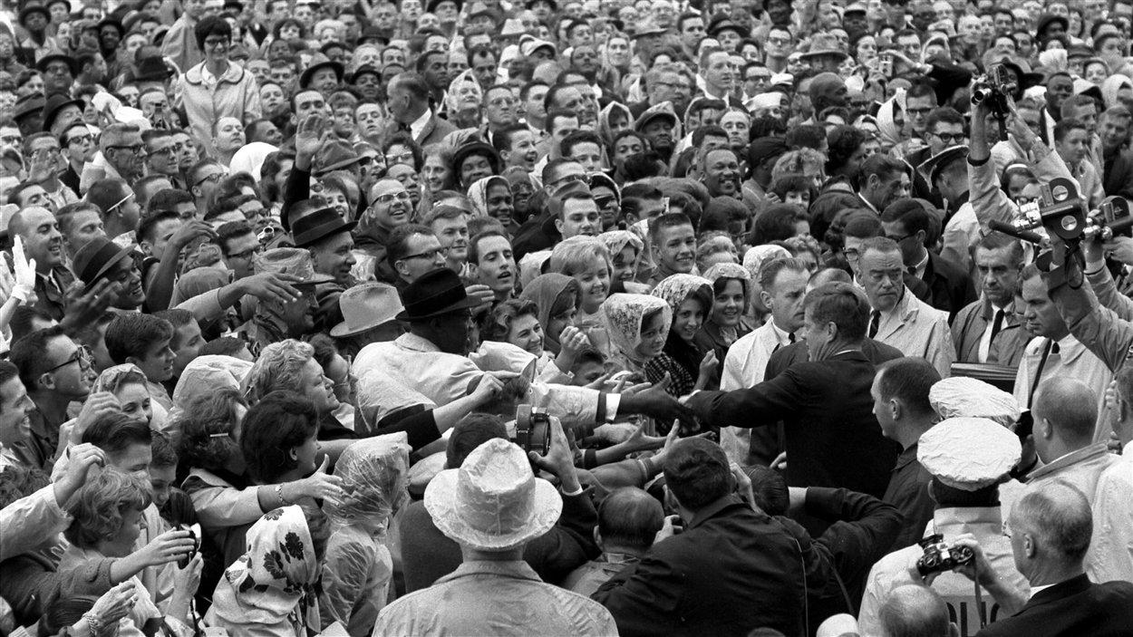 Le président John F. Kennedy tend la main à la foule réunie pour l'accueillir le 22 novembre 1963.