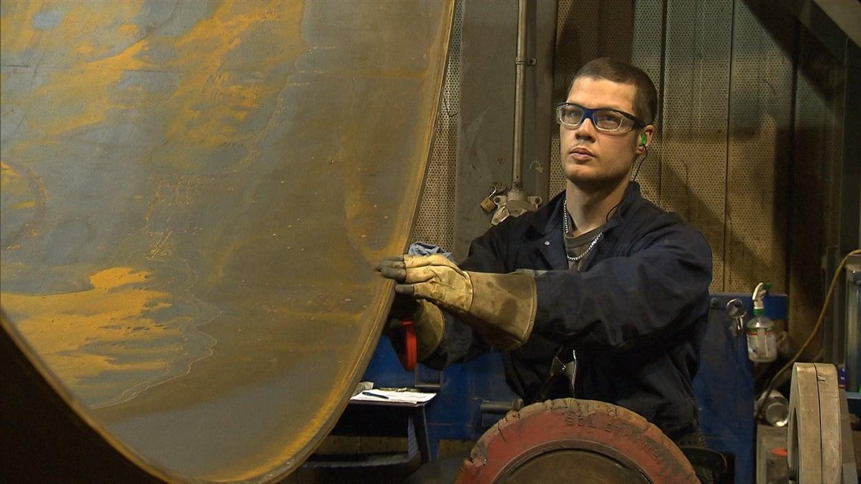 Un jeune travailleur dans une usine