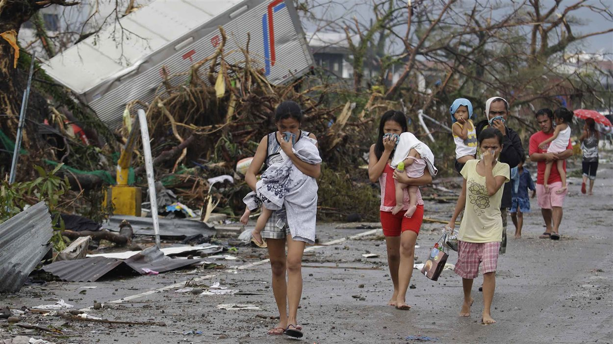 Des résidents de Leyte se couvrent le visage pour ne pas sentir l'odeur des cadavres.