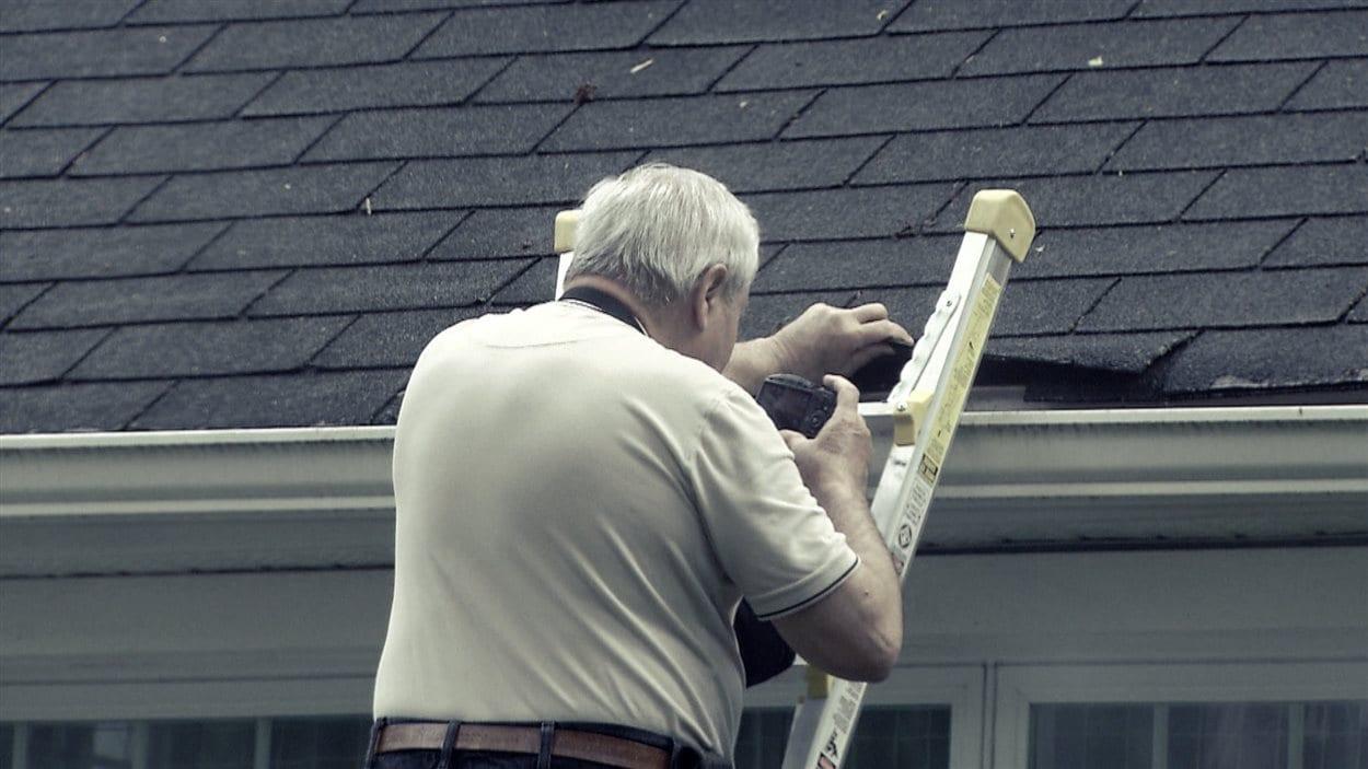 Un inspecteur en bâtiment examine la toiture d'une maison.