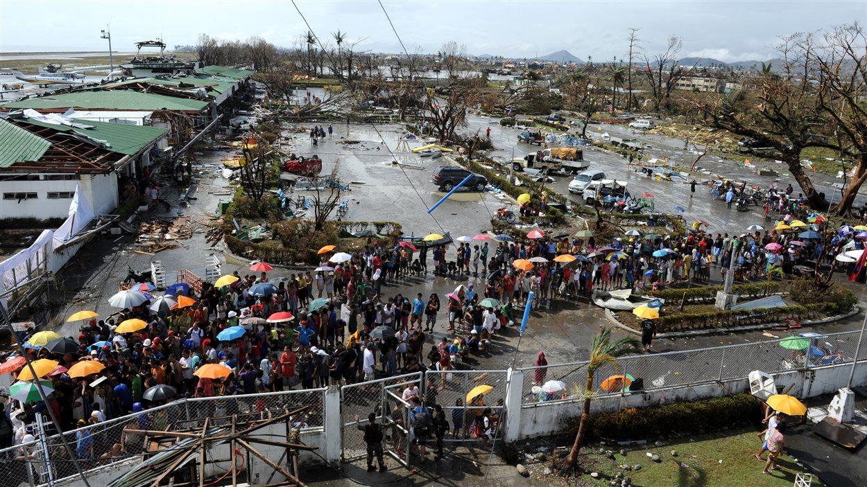 Des sinistrés font la queue pour obtenir de la nourriture et des biens de première nécessité à l'aéroport de Tacloban.