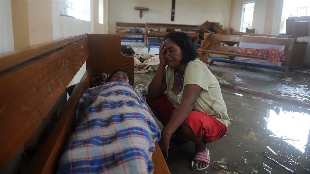 Une mère de famille pleure son fils mort dans une église inondée.