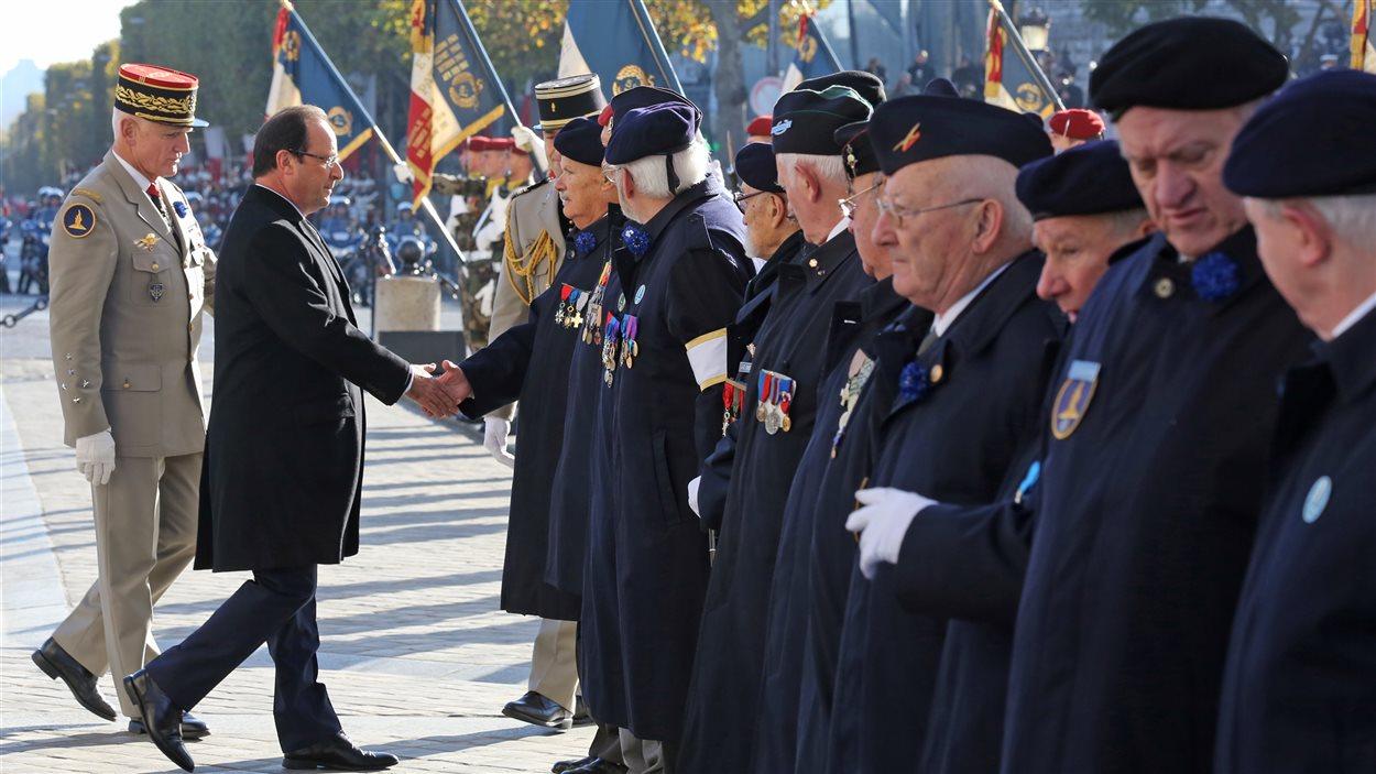 Le président français François Hollande salut des vétérans à Paris.